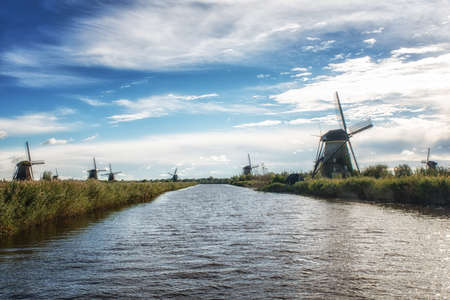 Colorful Autumn morning on the canal in Netherlands. Dutch windmills at Kinderdijk.