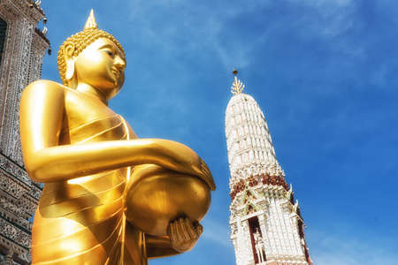 The sculpture of Golden Buddha is standing with both hands holding an alms bowl. Stock Photo