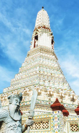 Spire and Guardian at Wat Arun Temple in Bangkok, Thailand Stock Photo
