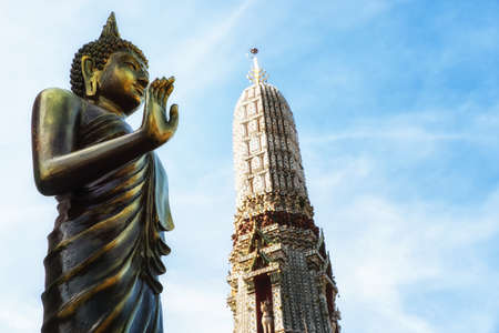 A Buddha statue with Prang (spire) at Arun Ratchawararam temple in Bangkok, Thailand