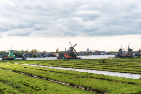 derives: windmills at Zaanse Schans, an industrial and national Dutch heritage site and famous tourist destination in the municipality of Zaandam, the Netherlands. Zaanse Schans is located on the river Zaan, from which its name derives. Industry in the background.