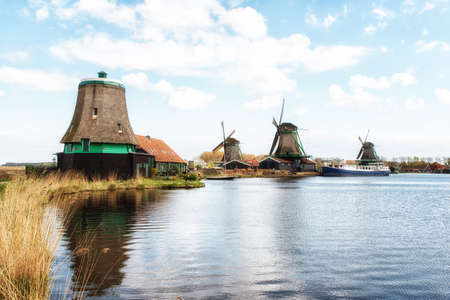 zaan: Authentic Zaandam mills on the water channel in Zaanstad willage. Zaanse Schans Windmills and famous Netherlands canals, Europe. Stock Photo