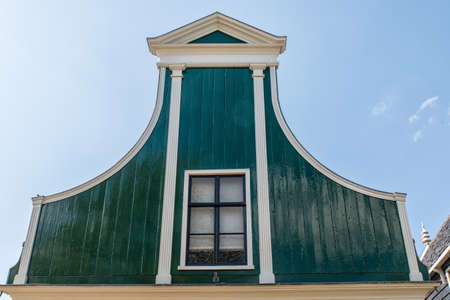 Roof detail of an Holland wooden house in green color with two white windows on a blue sky. Editorial