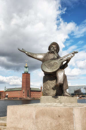 Stockholm, Sweden - May 11, 2017: Statue of Evert Taube, a Swedish author, artist, composer and singer, considered as one Swedens most respected musicians ever. with Stockholm City hall in background. Editorial