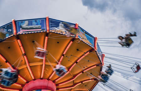 People ride a chairoplane in an amusement park
