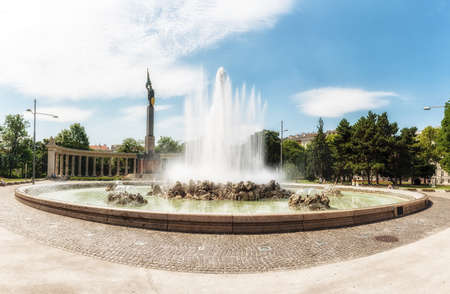 Vienna, Austria - July 9, 2017: People meander about Hochstrahl Fountain and the Soviet War Memorial in central Vienna. The Soviet War Memorial was unveiled in 1945 to commemorate the 17,000 Soviet solders who died in the Battle for Vienna of World War II