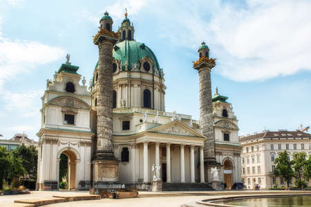 Vienna, Austria - July 9, 2017: The St. Charles's Church (Karlskirche) a 18th century baroque church in the centre of Vienna. The majestic landmark is highly frequented by tourists from all over the world resting at the lake. The lake is decorated with a  報道画像