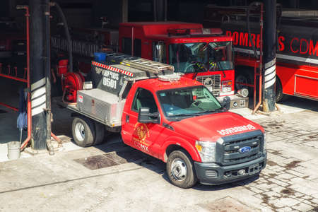 Mexico City, Mexico - February 15, 2018:  bright red shiny fire engine engines truck trucks at modern station ready to roll in response to alarm in Mexico City
