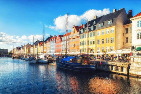 Copenhagen, Denmark, September 20, 2017: Nyhavn is a 17th-century waterfront, canal and entertainment district in Copenhagen, Denmark. it is lined by brightly coloured 17th and early 18th century townhouses and bars, cafes and restaurants. The canal harbours many historical wooden ships.