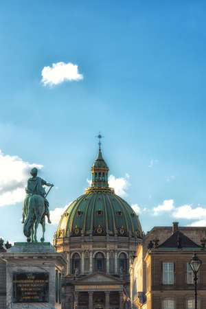 Frederik V of Denmark statue at  Copenhagen's Amalienborg or Royal Palace courtyard with dome of Marble church (Frederik's Church) behind in Copenhagen, Denmark