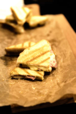A ham and cheese panini served on brown paper Banco de Imagens