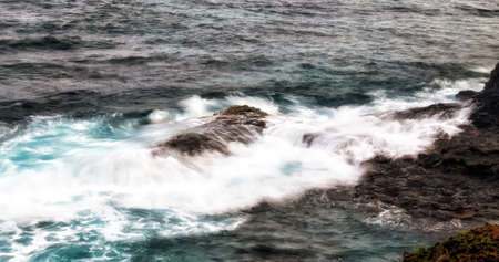 Waves crashing over the rocks in the surf at Rollas island in Sao tome and Principe Banco de Imagens