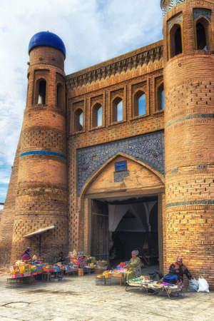 Khiva, Uzbekistan - October 13, 2015: The Islam Khoja Madrassa that nowadays serves as the museum, surrounded by numerous market stalls.