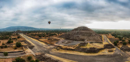 panoramic view of the ruins of Teotihuacan with colorful ballons in a sub valley of Mexico - The Avenue of the Dead and the pyramid of the sun and the moon  seen from a hot air balloon