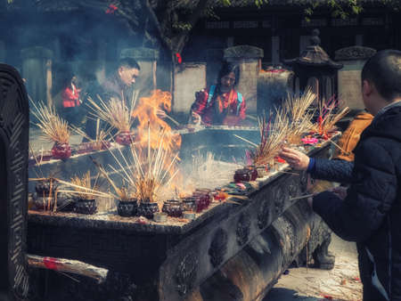 Chengdu, China - 05 February 2019: Crowds praying for blessings with incense sticks at the Zhaojue Temple complex, a Buddhist temple located in Chenghua District of Chengdu, Sichuan, China. Editorial