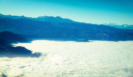 Aerial view of the Andes mountains, approaching Santiago, with early morning mist shrouding the landscape.