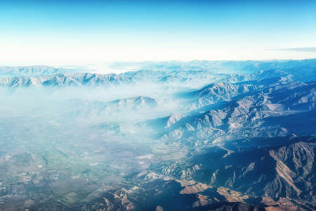 Aerial view of the Andes mountains, approaching Santiago, with early morning mist shrouding the landscape. Reklamní fotografie