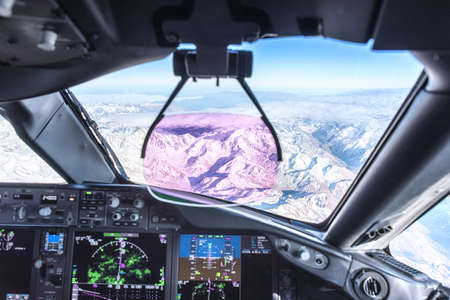 Modern commercial aircraft cockpit with Heads Up Display flying over the Andes near Chili.