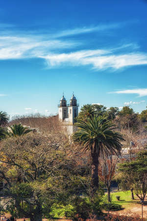 Church overlooking green landscape with blue sky in background, Colonia del Sacramento, Uruguay Stock Photo