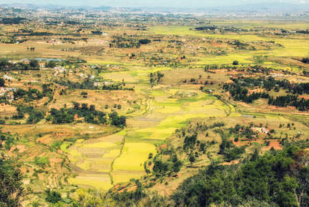 Just outside the highlands of Antananarivo, homes and agricultural fields stand on top of the heavily terraced hillsides with lush green rice paddy fields below standing in the muddy river valley.