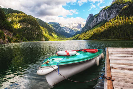 Beautiful Gosausee lake landscape with Dachstein mountains, boat, forest, clouds and reflections in the water in Austrian Alps. Salzkammergut region.
