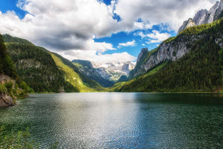 Sunny idyllic colorful summer alpine view. Lake Vorderer Gosausee is a peaceful mountain lake with clear transparent water and reflections. It's one of the three Gosausee lakes out there