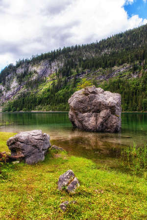 Idyllic, scenic view with dramatic cloud from bank on Vorderer Gosausee with big rock in the water. 版權商用圖片