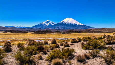 Parinacota and Pomerape Volcanoes above the horizon over Cotacotani lagoons waters an awesome and dramatic landscape inside Lauca National Park, Chile