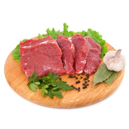 butchered: fresh raw beef steak meat on cutting board in closeup over white background