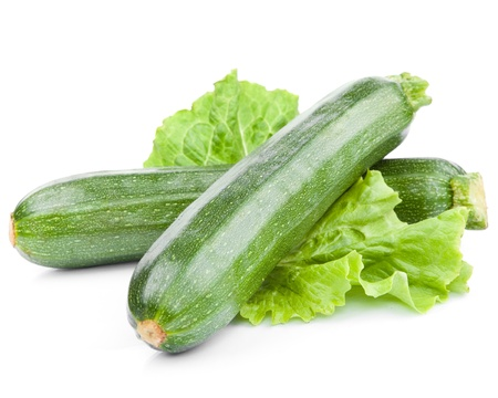 vegetable marrow: zucchini courgette decorated with green leaf lettuce  Isolated on white