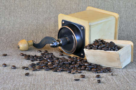 coffee grinder and coffee beans on the light brown texture