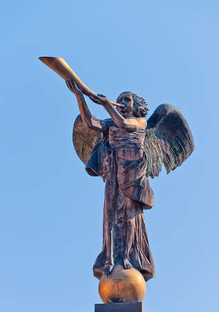statue of angel who play on the horn photo