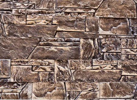 A wall of various shapes stone bricks as background Stock Photo