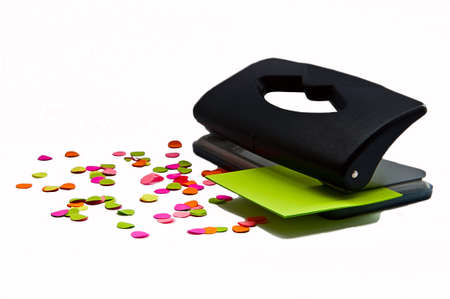 puncher: Black office puncher and pieces of colorful paper on the white background Stock Photo