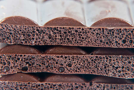 Black chocolate with bubbles lying in row