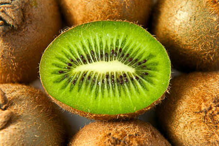 Half kiwi in the middle of other kiwis lying on the white surface Stock Photo