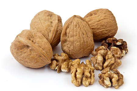 some covered and uncovered walnuts on the white background
