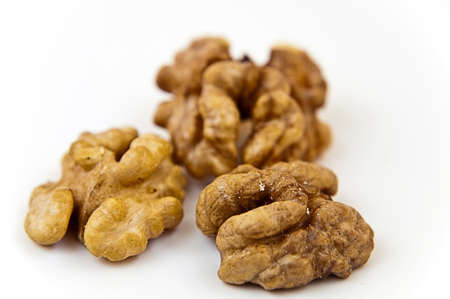 Three recovered walnuts on the white background