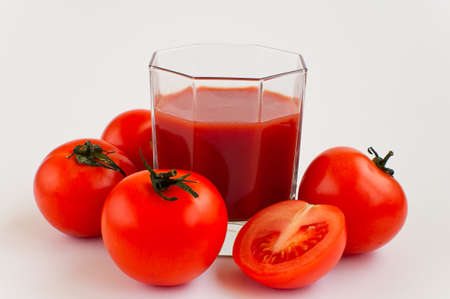 Glas of tomato juice and tomatoes aroud it on the white background