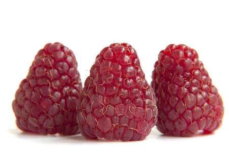 three red raspberries on a white background