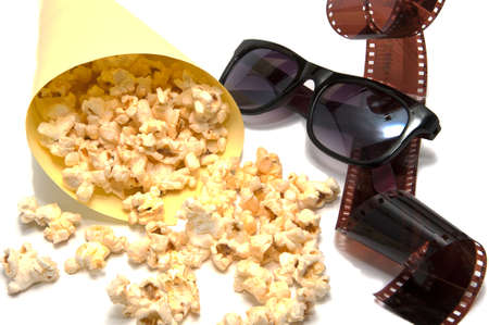 negatives: Isolated composition of movie themes stuff: glasses, popcorn and negatives. Stock Photo