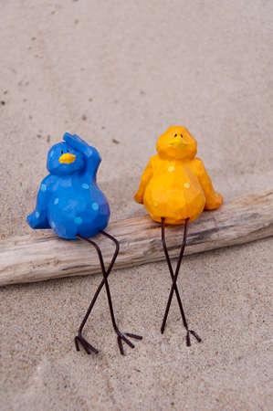 a pair of birds are sunbathing on the beach