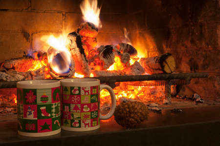 Cristmas cups and fire in the fireplace