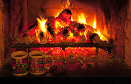 fire  in the fireplace and two christmas cups Stock Photo
