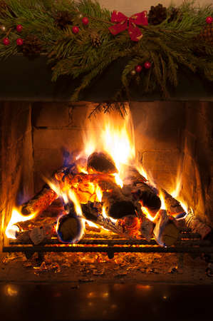 Fire in the fireplace and christmas decoration above