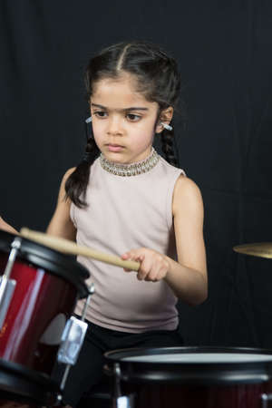 5 year old practices on the drums.