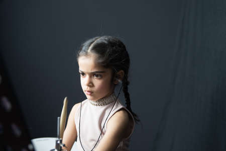 5 year old girl practices the drums.