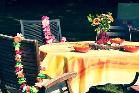 Table decorated in a Hawaiian theme - garlands and flowers. Imagens