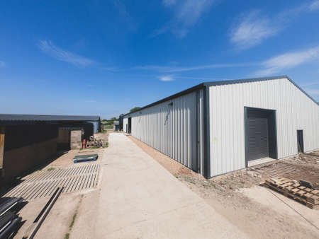 Wide angle view of the outside of a warehouse on a backdrop of blue sky.