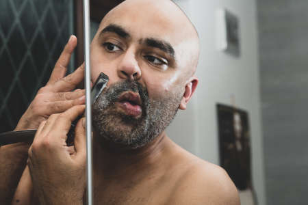 A bald, British Asian man, grooming and sculpting his beard at home in the bathroom, in front of the mirror. He is using a traditional cut throat razor or a barber's razor. This can be used to theme issues around maleness, dating and middle age. Stockfoto